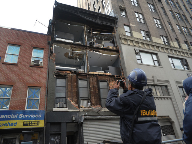 <p>A Department of Buildings official looks at the partial collapse of a Chelsea apartment building on Tuesday Oct. 30, 2012.</p>