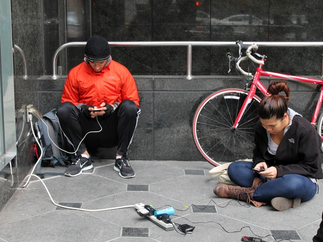 <p>Residents who lost power at home during Hurricane Sandy were desperate to charge their cell phones and gadgets on Wednesday. Here, people plug in to an outlet outside of a building in midtown east.</p>