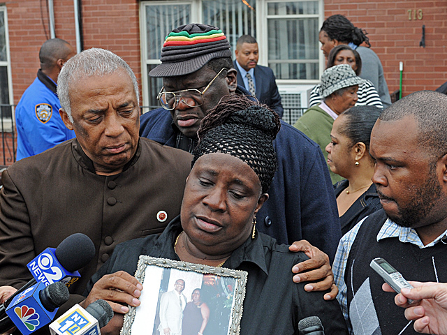 <p>June Facey, wife of 52-year-old Raymond, who was shot on Tuesday, Oct. 23, 2012, clutches a photo of her and her husband.</p>