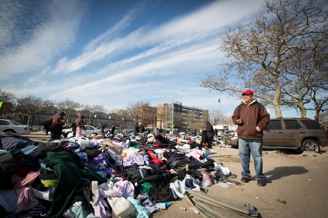 <p>Eddie Pizarro, 54, a tow truck driver stands next to a mountain of donated clothes in the Rockaways after Hurricane Sandy. He has been boiling water on his stove to keep warm at his apartment.</p>