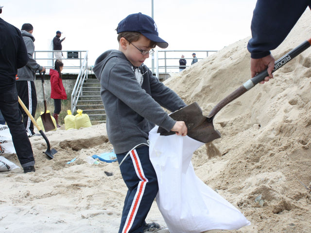 <p>Finnian Sullivan holds onto a bag while his dad, Matt Sullivan, shovels sand into it at the Rockaways, Oct. 28, 2012.</p>