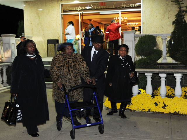<p>Glenda Moore&#39;s godmother, wearing a patterned coat, leaves the funeral home Nov. 8, 2012, after the wake for Brendan and Connor Moore, 2 and 4, who drowned during Hurricane Sandy.</p>