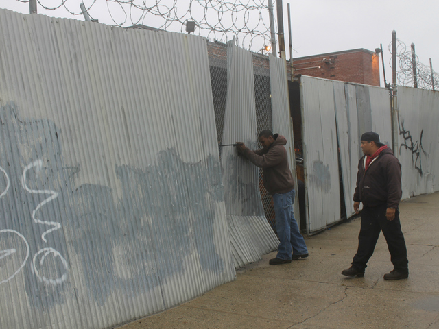 <p>Verizon workers try to secure corrugated metal attached to fence outside the phone company&#39;s building on Carroll Street in Gowanus.</p>