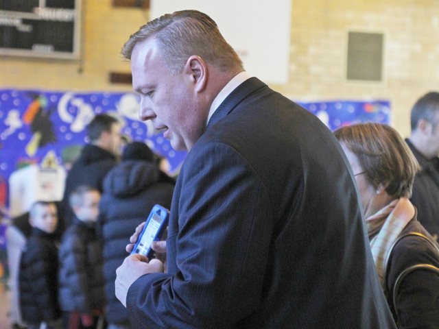 <p>City Councilman Dan Halloran helps a voter find her election district at P.S. 184 in Whitestone on Nov. 6.</p>