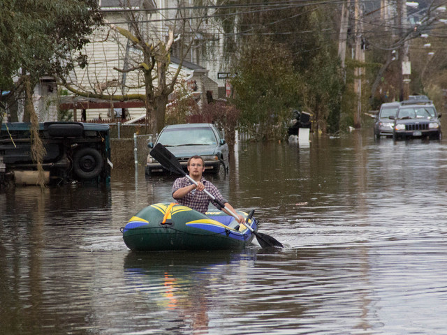 <p>A man rows to his home on Hunter Avenue in Midland Beach after Hurricane Sandy hit, Oct. 31, 2012.</p>