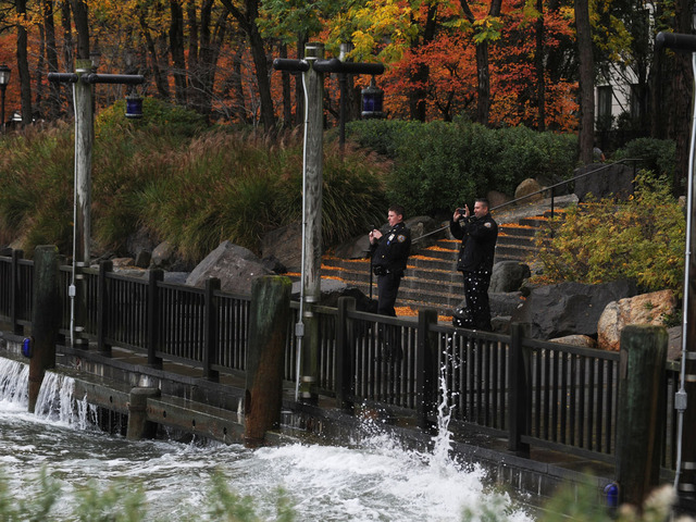 <p>Two NYPD officers take photos of the storm surge along the Hudson River near Battery Park in lower Manhattan.&nbsp;</p>