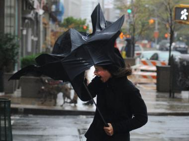 A woman loses control of her umbrella during a storm. A winter storm bringing snow and rain is threatening to delay post-Christmas travel on Dec. 26.