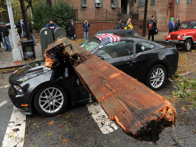 <p>Paul Ugactz stands by his black Mustang, which was buried under the large wooden beam at East 20th Street near the East River.</p>