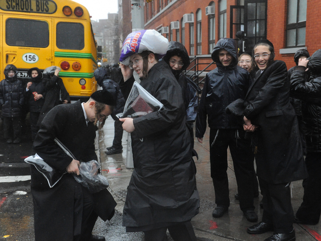 <p>Hasidic boys returning from school struggle to stay dry</p>