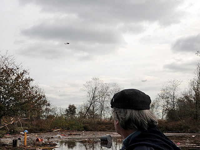 <p>Patrick Casalaspro, 51, watches a helicopter fly near his New Dorp Beach home in Staten Island after Hurricane Sandy, Nov. 1, 2012.</p>