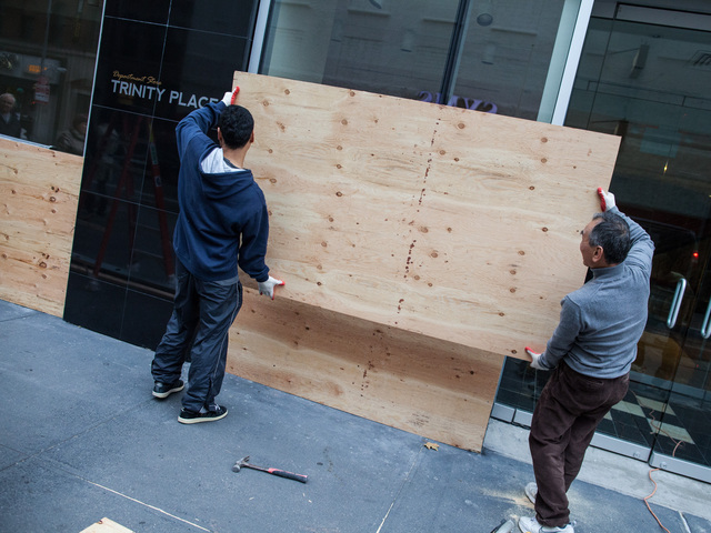 <p>Workers covered a Downtown storefront windows with plywood sheets to protect the glass from the expected onslaught of Hurricane Sandy on Oct. 28, 2012.</p>