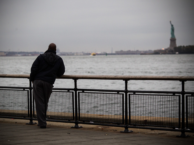 <p>A man looked out over New York Harbor toward the Statue of Liberty in advance of Hurricane Sandy&#39;s arrival on Oct. 28, 2012.</p>
