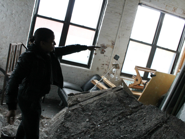<p>Jamie Jones, owner of New York Graphics Studio, points out damage her business sustained after Sandy caused her ceiling to collapse.</p>