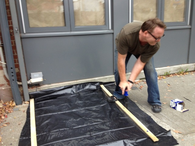 <p>Architect Jim Cameron, 42, used plastic tarp, wood planks and a fastener to seal the cellar hatch outside his building on Van Brunt Street on October 28, 2012.</p>