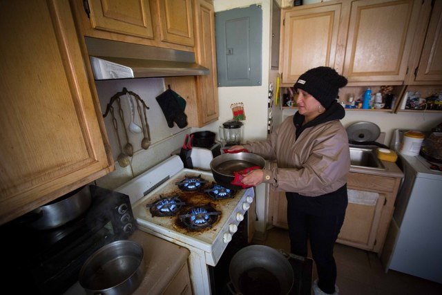 <p>Kisha James, 38, put water on the stove as a way to heat up her three-bedroom apartment by Beach 64th Street in the Rockaways on Nov. 5, 2012 after Hurricane Sandy.</p>