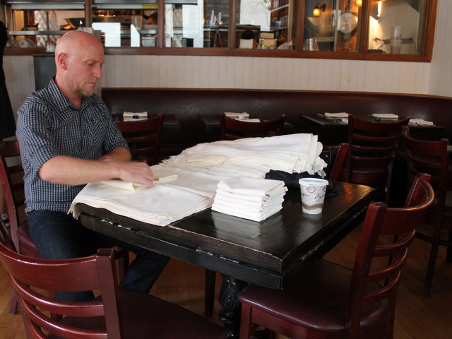 <p>A worker folds napkins at Little Owl restaurant in Greenwich Village as it got ready to open on Saturday for the first time since the power outage caused by Hurricane Sandy.</p>