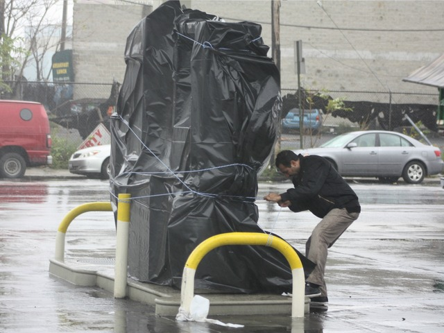 <p>A man secured a Greenpoint gas station as winds ripped through on Monday October 29, 2012.&nbsp;</p>