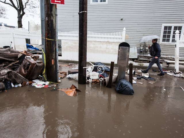 <p>A man walks through the rising flood waters in Rockaway Beach on Nov. 7, 2012.</p>