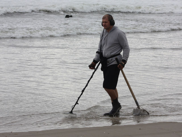 <p>A man uses a metal detector on the beach at Breezy Point, Oct. 28, 2012.</p>