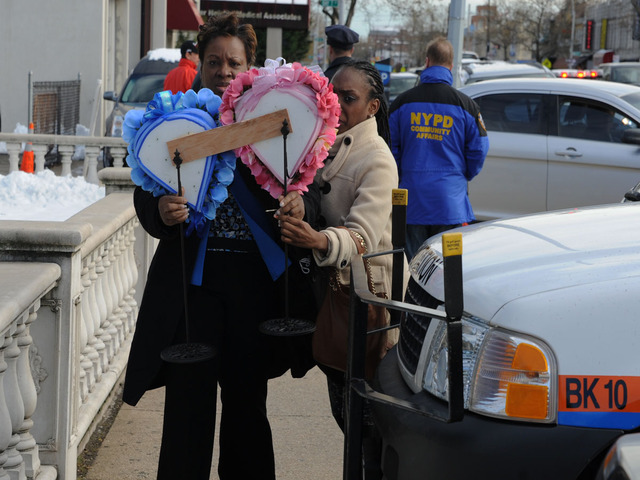 <p>Women enter the funeral home with a flower arrangement in the shape of two hearts for the Nov. 8, 2012 wake for Brendan and Connor Moore, 2 and 4, who died during Hurricane Sandy.</p>