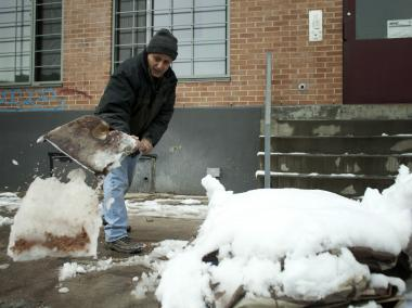 Eddy Giar shovels a sidewalk after a Nor'easter it the city on Nov. 8, 2012.