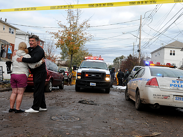 <p>Grieving neighbors embraced where the body of a disabled man was removed from his Nugent Avenue home in Staten Island on Oct. 31, 2012.</p>