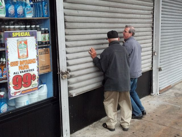 <p>Workers re-open a bodega on Washington Avenue.</p>