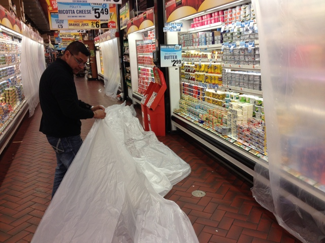 <p>Manager Jose Delarosa, 41, hangs plastic covers over refrigerated shelves in the dairy aisle at the Red Hook Fairway. The covers will help keep the shelves cool when the store stays closed Monday. The last time the store had to hang these covers because it was staying closed was for Irene last year</p>