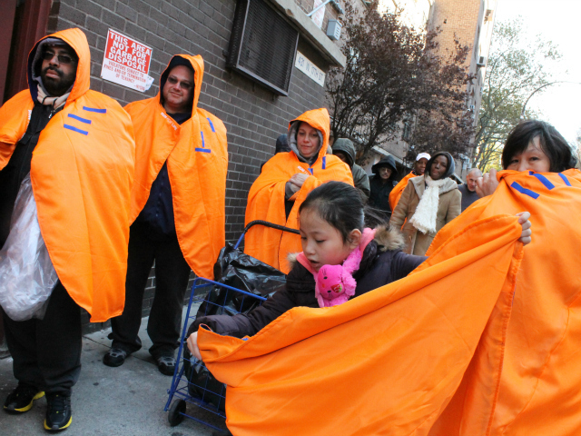 <p>People lined up for free food, water and toiletries that the National Guard delivered to the Robert Fulton Houses on Monday, Nov. 5, 2012. Volunteers passed out insulated ponchos originally intended for runners in the city&#39;s canceled marathon.</p>