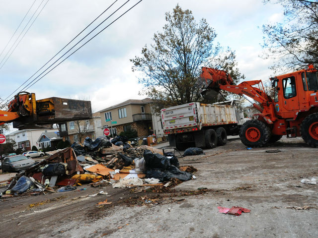 <p>Sanitation crews clean up wreckage from Hurricane Sandy in Midland Beach. The Department of Sanitation will end their storm debris collection on January 14, 2013.</p>
