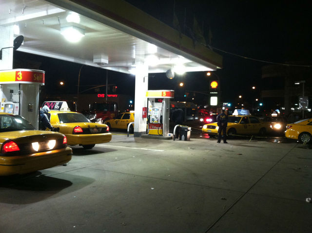 <p>A city official watches as cabs pour into the Shell Station in Jackson Heights.</p>