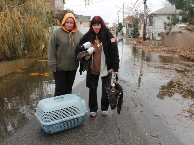 <p>October 31, 2012 - Two women carry their cat from their home on Fox Beach Lane.</p>