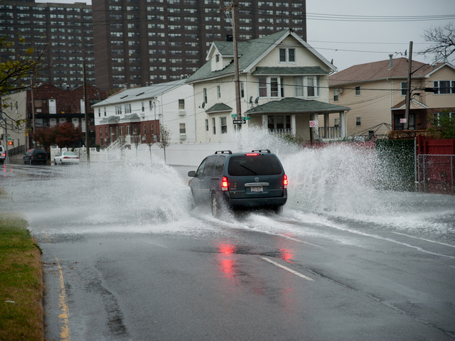 <p>A car navigates flood waters on Seagirt Boulevard at Beach 28th Street in Far Rockaway on Monday October 29th, 2012.</p>