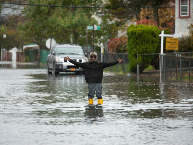 <p>A resident walks through flood waters on Beach 29th Street in Far Rockaway on Monday October 29th, 2012.</p>