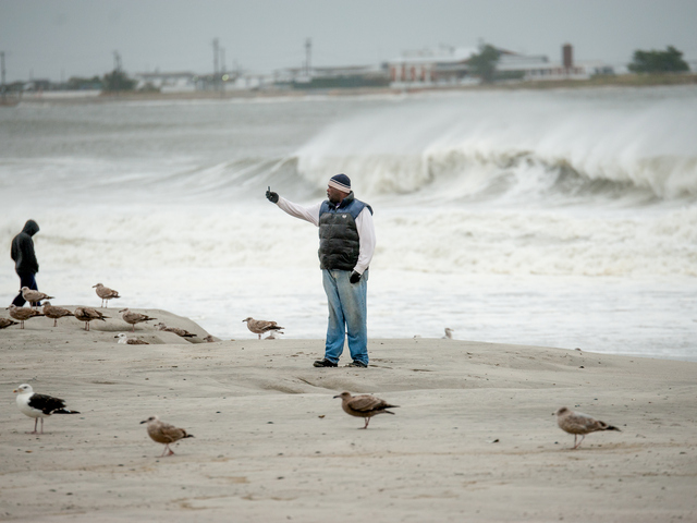 <p>A man takes photos near Beach 32th Street in Far Rockaway on Monday October 29th, 2012.</p>