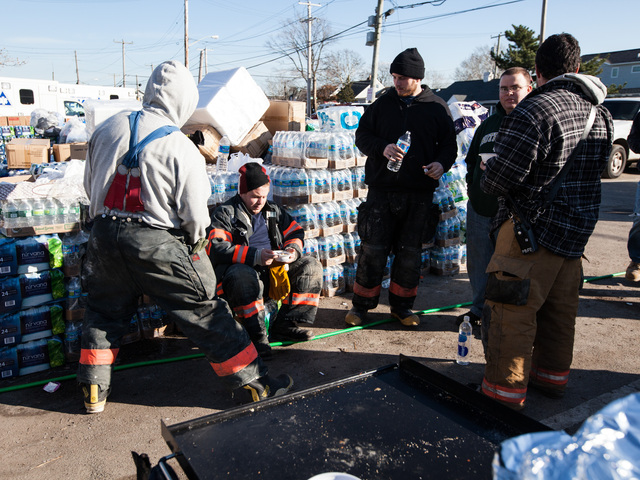 <p>Volunteer firefighters of Rockaway Point Volunteer Fire Dept. and local residents take a break while distributing supplies to the local community in Rockaway Point Nov. 5th, 2012.</p>