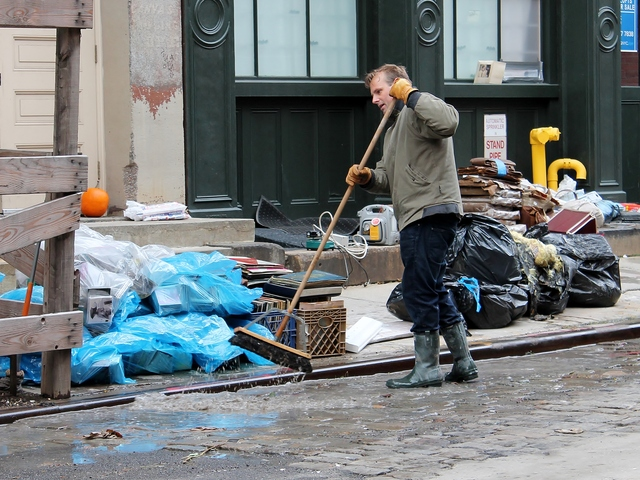 <p>A man sweeps water in the South Street Seaport on Thursday, Nov. 1, as the neighborhood struggled to clean up damage from flooding during Hurricane Sandy.</p>