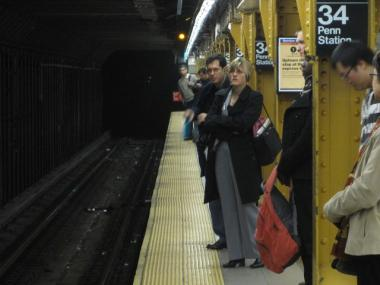 Commuters wait for the 1 train at the 34th Street station.