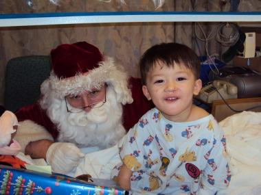 FDNY Santa Claus brings presents to an ill child at Beth Israel Medical Center.