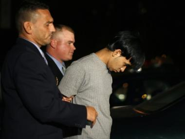 Syed Rahman (r.) is escorted to a car by police after being arrested on Aug. 7, 2008 for allegedly killing a patron of the popular Times Squares karaoke club Spotlight.