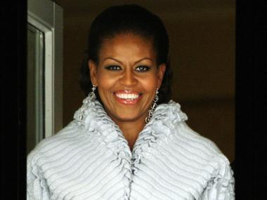 First Lady Michelle Obama smiles from behind bullet proof glass on the balcony of the Grand Hotel after waving to the crowds who had gathered outside for the traditional torchlight procession on December 10, 2009 in Oslo, Norway.