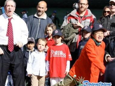 Margaret Chin throws out a ceremonial first pitch as Scott Stringer and others cheer.