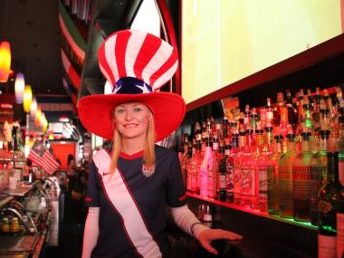 Patriotic bartender Alison Ryanm 34, keeps beers filled during the soccer match at Tonic sports bar in Midtown.