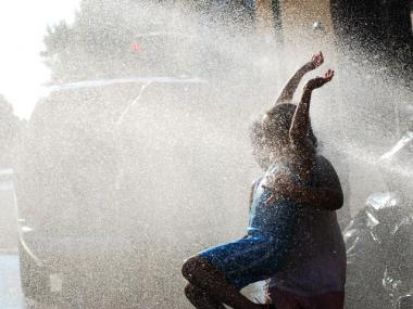 Children play in fire hydrants to cool off in the July heat.