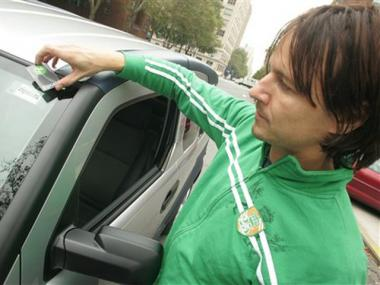New York Zipcar customer Thomas Bliven, 40, uses his Zipcard to unlock a shared car.