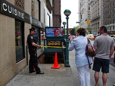 A NYPD officer stands guard outside the 57th Street NQRW subway stop while police respond to a report of a suspicious package in the station on Thursday, May 6, 2010