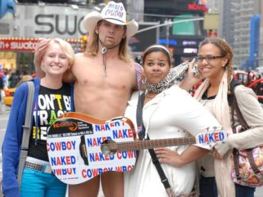 Naked Cowboy, Robert Burck, seen posing with Times Square visitors, has turned his act into a franchise.