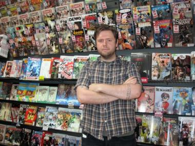 Thor Parker, assistant marketing director at Midtown Comics, stands in front of the new release wall at the Times Square location. Midtown Comics' new shop on Fulton Street will offer even more comic books.