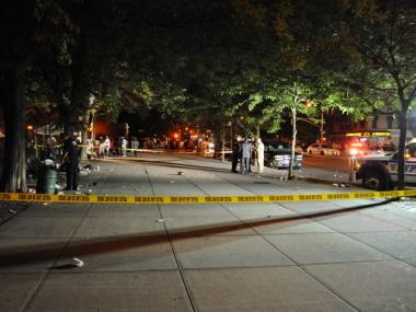 Police investigate the crime scene at 144 Street and Lenox Avenue after three people were shot and woman stabbed on Sunday, June 20, 2010.