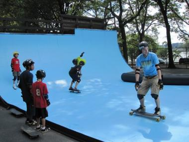Raymond Robinson, in blue, shows off his long board moves to fellow skaters at Riverside Park's skate park. Officials say they skate park needs a $750,000 renovation, but there's no funding for the project.